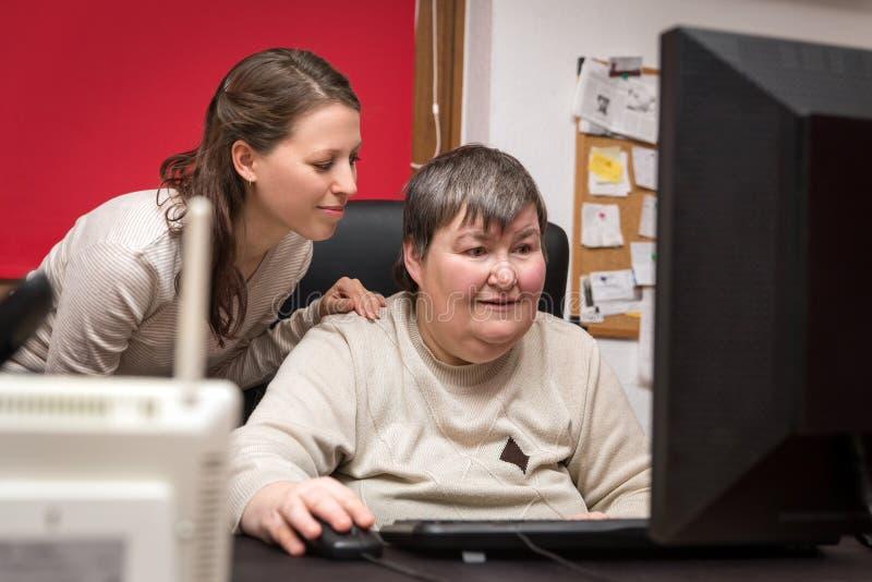 Cuidador e mentalmente - mulher deficiente que aprende no computador foto de stock