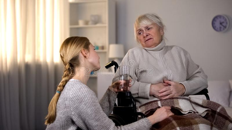 Cuidador fêmea que apoia a avó doente que guarda o vidro da água, hospital fotografia de stock