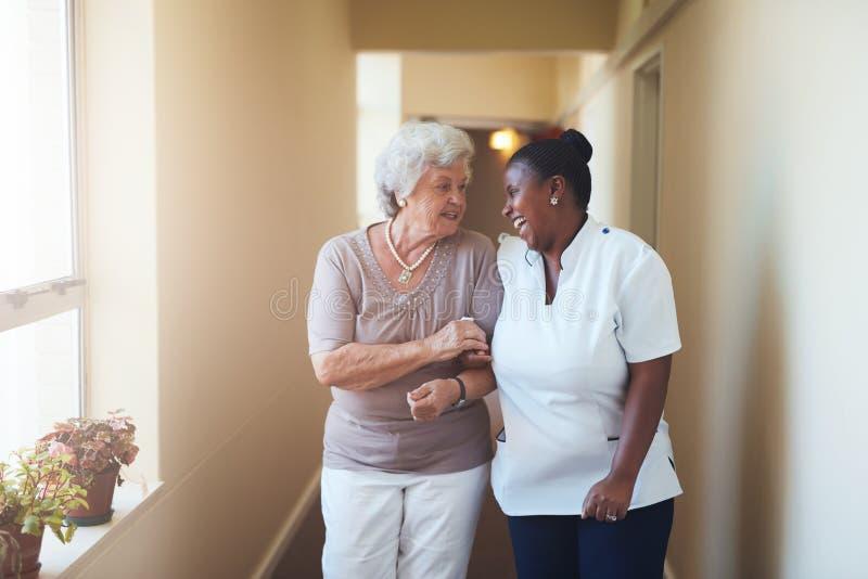 Cuidador femenino feliz y mujer mayor que caminan junto imagen de archivo libre de regalías