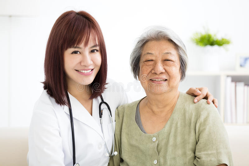 Cuidador home de sorriso com mulher superior fotografia de stock