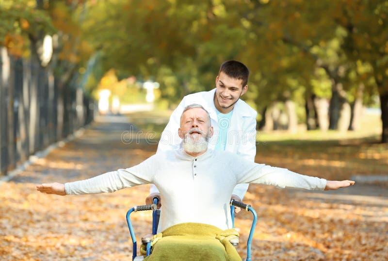Cuidador joven que camina con el hombre mayor foto de archivo