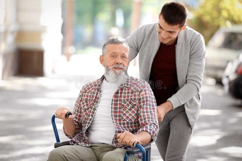Cuidador joven que camina con el hombre mayor fotos de archivo