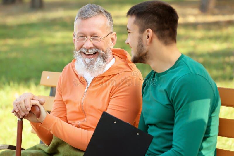 Cuidador joven que se sienta con el hombre mayor en banco imagenes de archivo