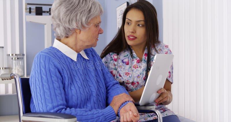 Cuidador latino-americano que compartilha da tabuleta com o paciente idoso foto de stock