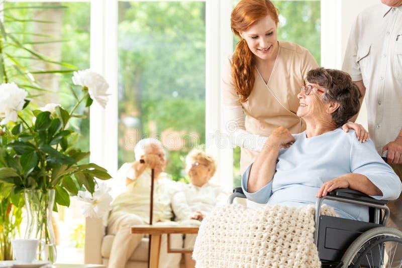 Cuidador macio que diz adeus a um pensionista idoso em um whe imagem de stock royalty free