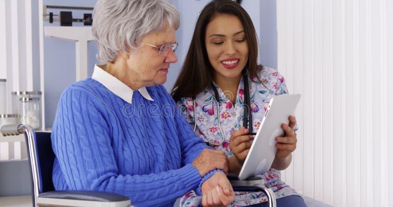 Cuidador mexicano que compartilha da tabuleta com o paciente idoso fotos de stock royalty free