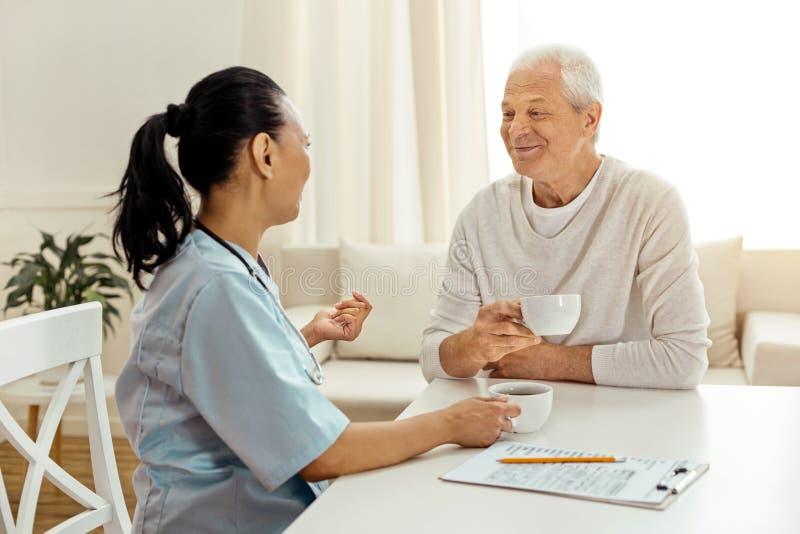 Cuidador positivo e paciente agradáveis que comem o chá fotos de stock royalty free