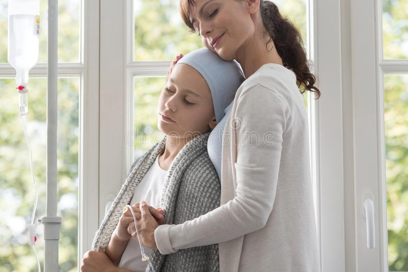 Cuidador que abraça a criança doente com o lenço vestindo do câncer imagem de stock royalty free