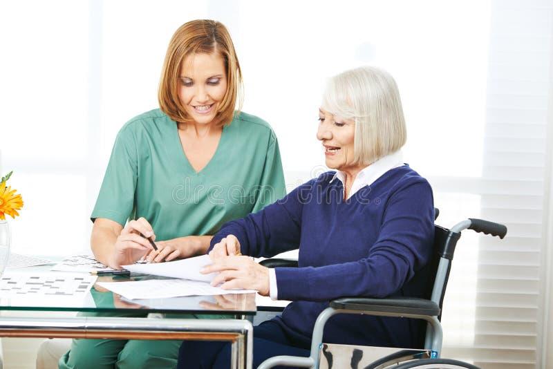 Cuidador que ayuda a la mujer mayor con los contratos imagen de archivo