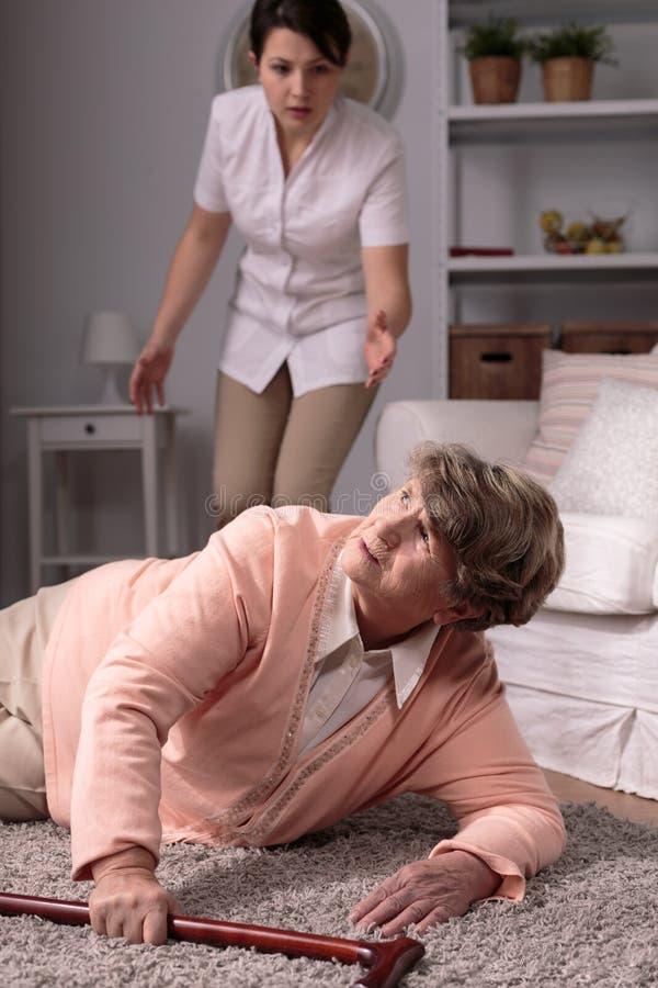 Cuidador que ayuda a la mujer mayor herida imagen de archivo