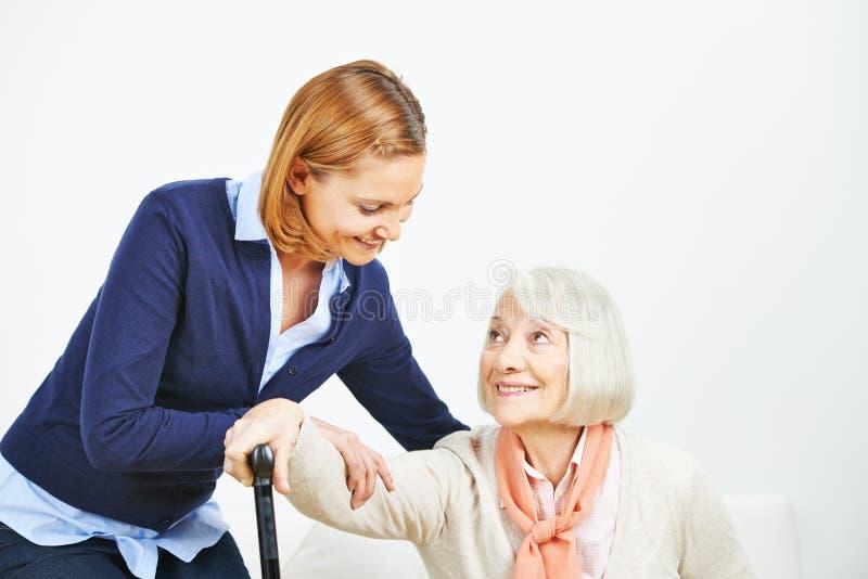Cuidador que ayuda a la mujer mayor que se levanta fotos de archivo libres de regalías