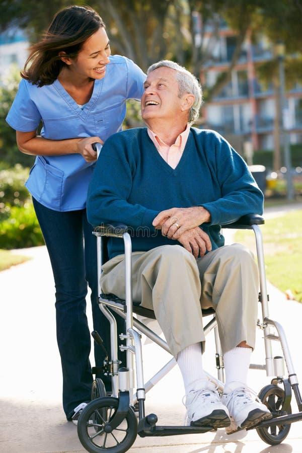 Cuidador que empuja al hombre mayor en silla de ruedas fotografía de archivo libre de regalías