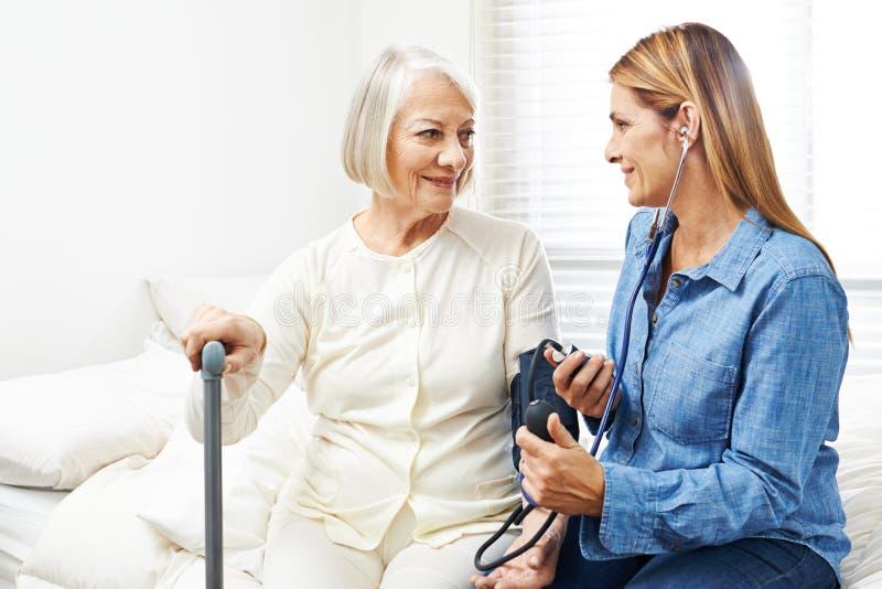 Cuidador que faz a monitoração da pressão sanguínea para a mulher superior foto de stock