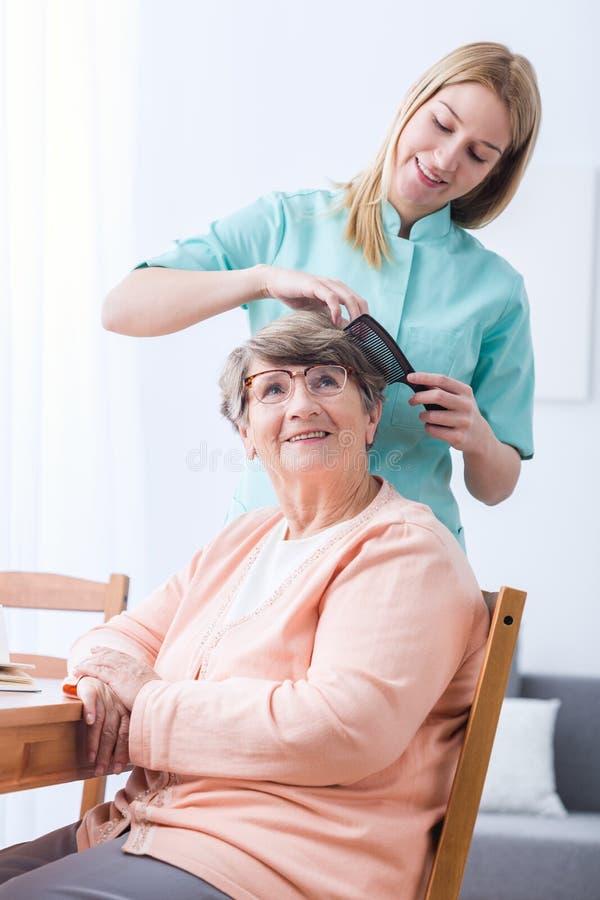 Cuidador que hace el pelo de la mujer mayor imagen de archivo