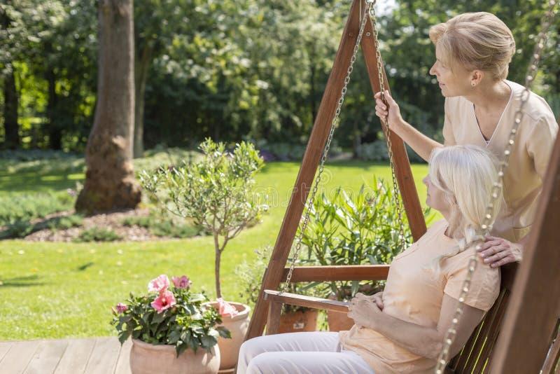 Cuidador sonriente y mujer mayor feliz en la terraza durante día soleado fotos de archivo