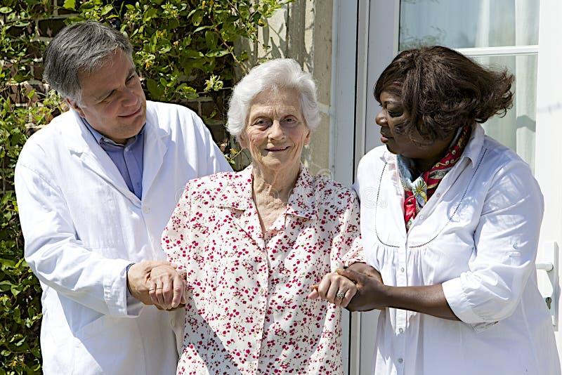Cuidadores que ayudan a caminar paciente mayor afuera imagen de archivo libre de regalías