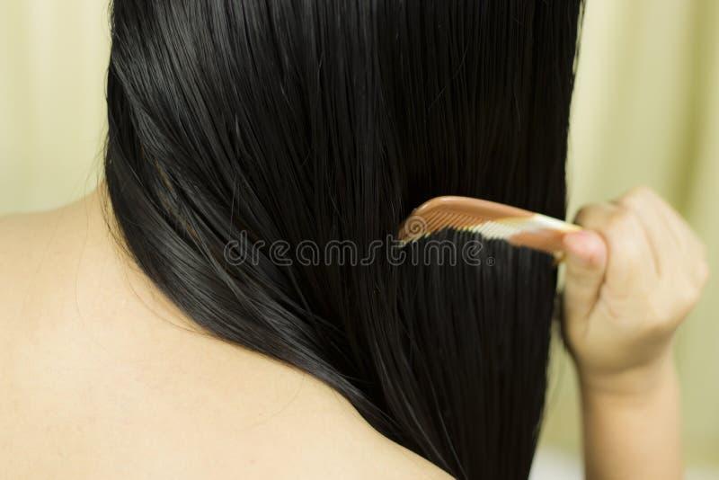 Cuidados capilares Close up do cabelo bonito de Hairbrushing da mulher com escova Retrato da mulher f?mea 'sexy' que escova por m imagem de stock royalty free