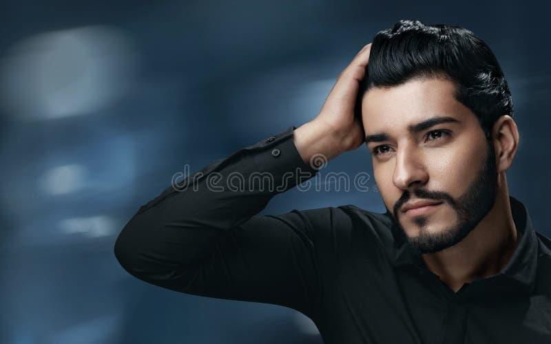Cuidados capilares dos homens Homem considerável com cabelo saudável tocante da barba imagem de stock royalty free