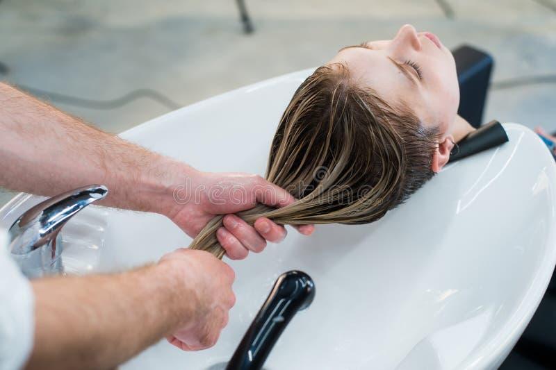 Cuidados capilares no salão de beleza moderno dos termas Cabeleireiro masculino que lava os cabelos adolescentes da menina imagem de stock royalty free