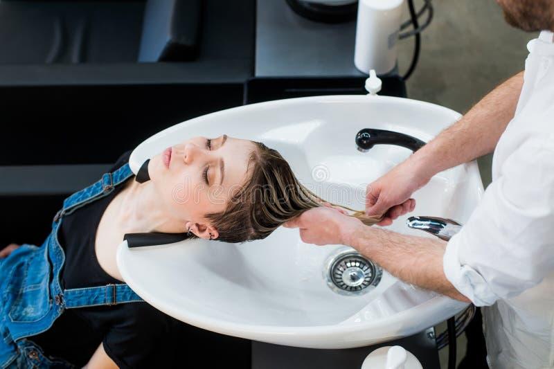 Cuidados capilares no salão de beleza moderno dos termas Cabeleireiro masculino que lava os cabelos adolescentes da menina imagem de stock