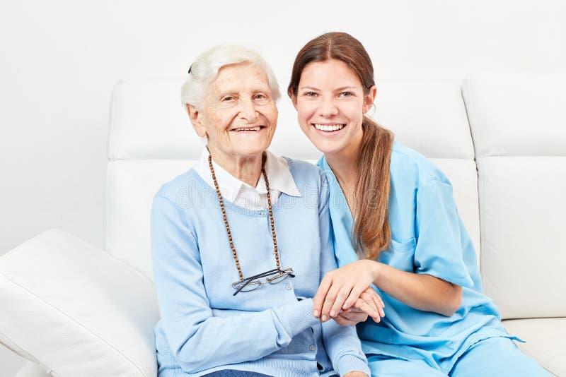 Cuidados com a mulher idosa feliz em casa imagem de stock