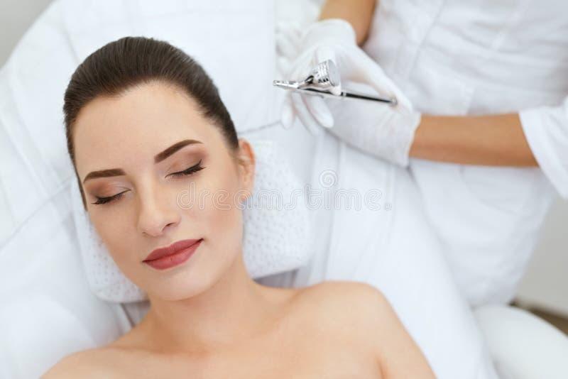 Cuidados com a pele da cara da beleza Mulher que obtém o tratamento do pulverizador do oxigênio imagem de stock royalty free