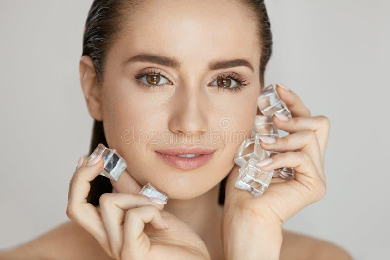 Cuidados com a pele da cara Mulher que aplica cubos de gelo imagens de stock royalty free