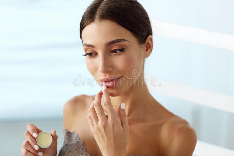 Cuidados com a pele dos bordos Mulher com a cara da beleza que aplica o bálsamo de bordo sobre imagem de stock royalty free