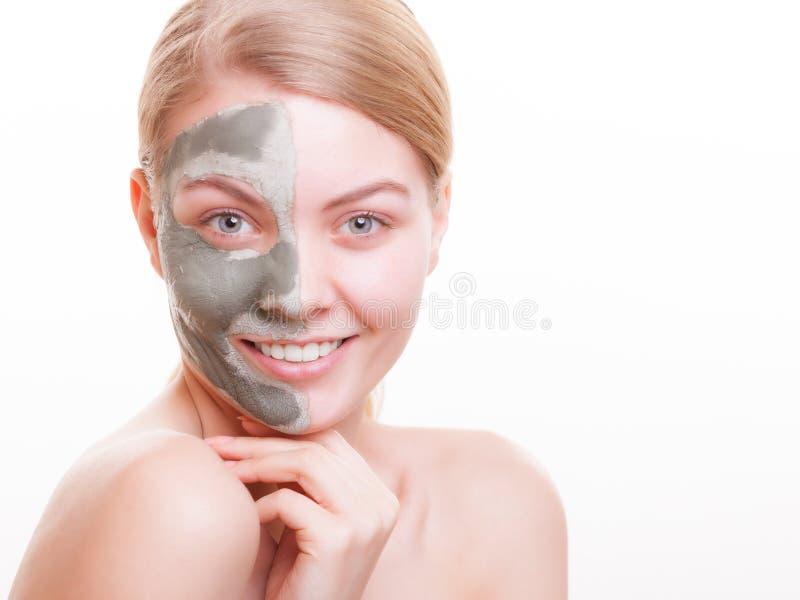 Cuidados com a pele. Mulher que aplica a máscara da argila na cara. Termas. foto de stock