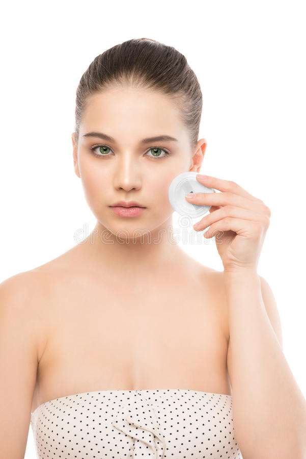 Cuidados de la mujer joven para la piel de la cara Piel fresca perfecta de limpieza usando el cojín de algodón Aislado foto de archivo libre de regalías