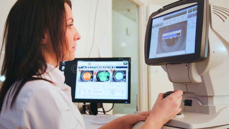 Cuidados médicos alta-tecnologias - oftalmologista na clínica de olhos que faz o diagnóstico com visão do paciente pelo computado imagens de stock