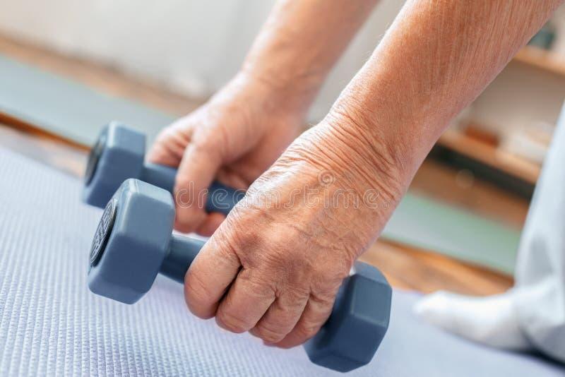 Cuidados médicos do exercício do homem superior em casa que mantêm o close-up dos pesos imagens de stock