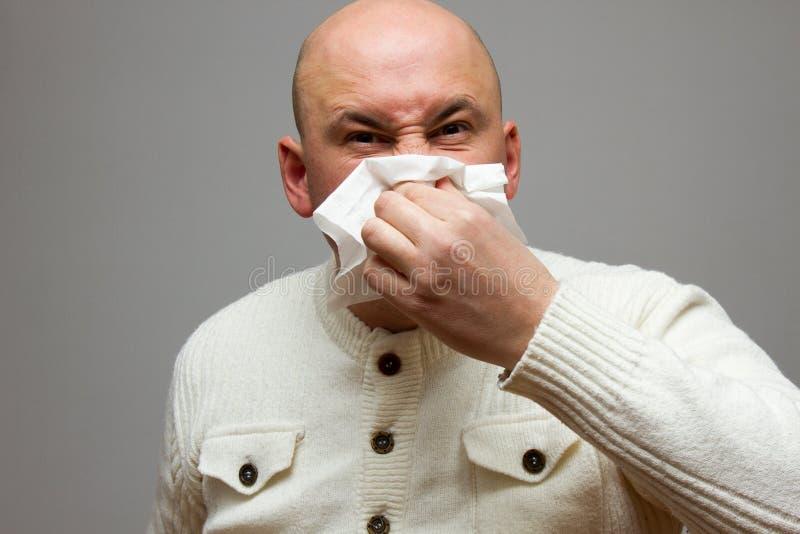 Cuidados médicos, gripe, higiene e conceito dos povos - homem superior doente com a limpeza de papel que funde seu nariz em casa fotos de stock