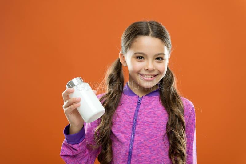Cuidados médicos Suplementos à vitamina da tomada Garrafa longa das medicinas da posse do cabelo da menina Conceito da vitamina P imagens de stock