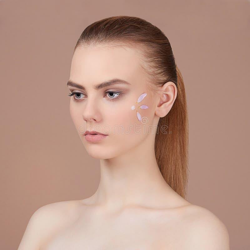 Cuidados rubios jovenes de la mujer para la cara fotos de archivo