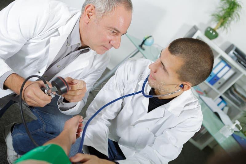 Cuide al aprendiz joven de enseñanza cómo tomar la presión arterial imagenes de archivo