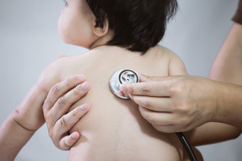 Cuide al bebé asiático de examen y escuche su golpe de corazón foto de archivo libre de regalías