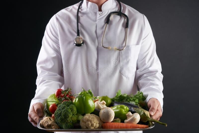 Cuide al nutricionista que sostiene una bandeja de verduras orgánicas frescas imágenes de archivo libres de regalías