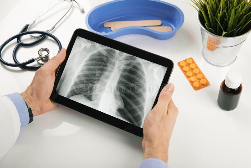 Cuide analizar resultados pacientes de la radiografía del pulmón en la tableta digital fotos de archivo