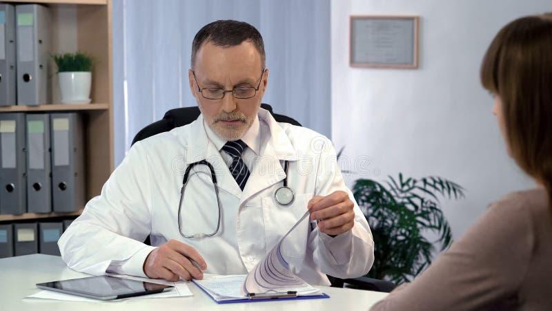 Cuide el boletín de inscripción de la lectura, comprobando el análisis, diciendo diagnosis a la mujer fotografía de archivo