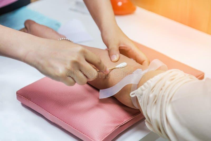 Cuide el brazo paciente limpio del ` s con la esponja del alcohol que prepara la inyección para la muestra del dibujo de la sangr imagenes de archivo