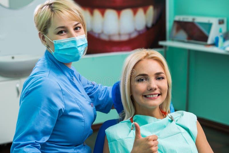 Cuide el dentista y el pulgar paciente femenino feliz de la demostración para arriba en la clínica dental fotografía de archivo libre de regalías