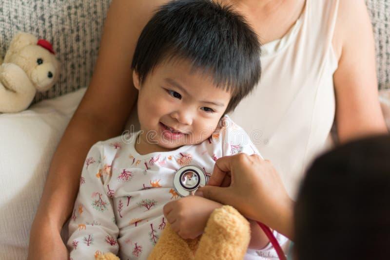 Cuide el examen de una muchacha del niño en un hospital con su mamá imagen de archivo libre de regalías