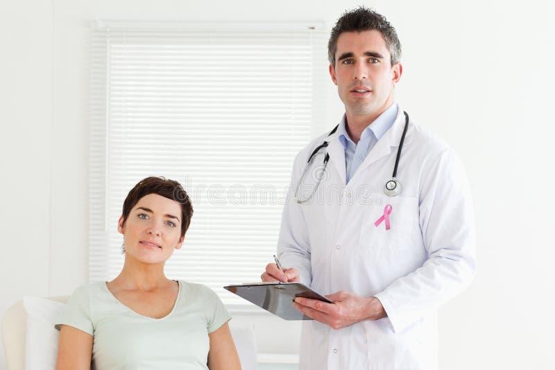 Cuide el hombre con la cinta de la conciencia del cáncer de pecho y al paciente fotografía de archivo