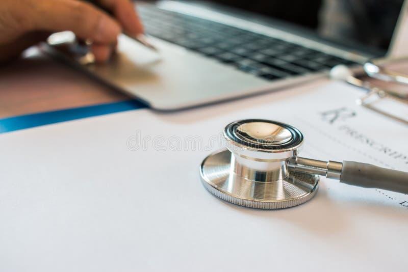 Cuide el ` s que trabaja en el ordenador portátil, escribiendo el tablero de la prescripción con las carpetas del papel de inform foto de archivo