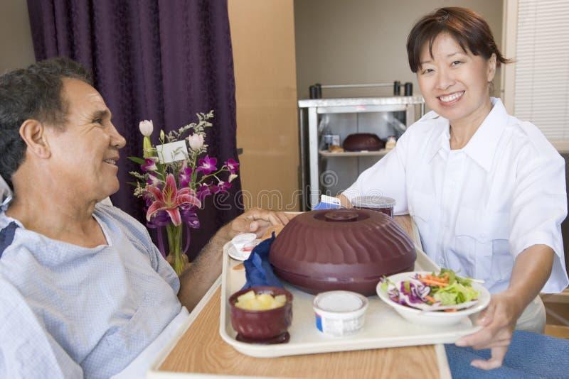 Cuide el servicio un paciente de una comida en su cama fotos de archivo