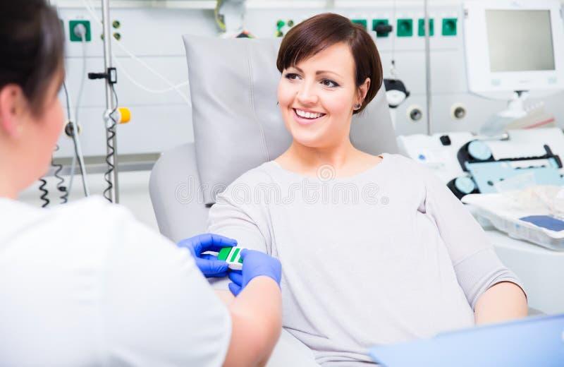 Cuide en el hospital que comprueba el acceso en el donante de sangre de la mujer imagen de archivo