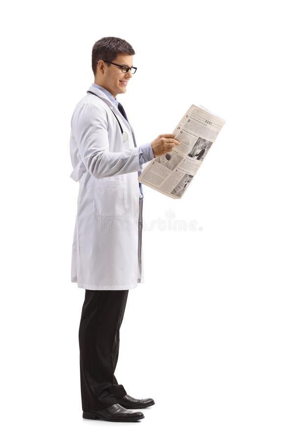 Cuide esperar en línea y la lectura de un periódico foto de archivo