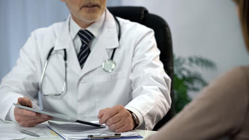 Cuide hablar con el paciente, sosteniendo la tableta con la información del análisis, diagnosis foto de archivo
