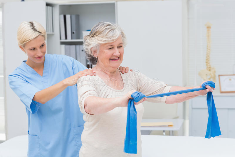Cuide la ayuda del paciente mayor en el ejercicio con la banda de la resistencia fotos de archivo